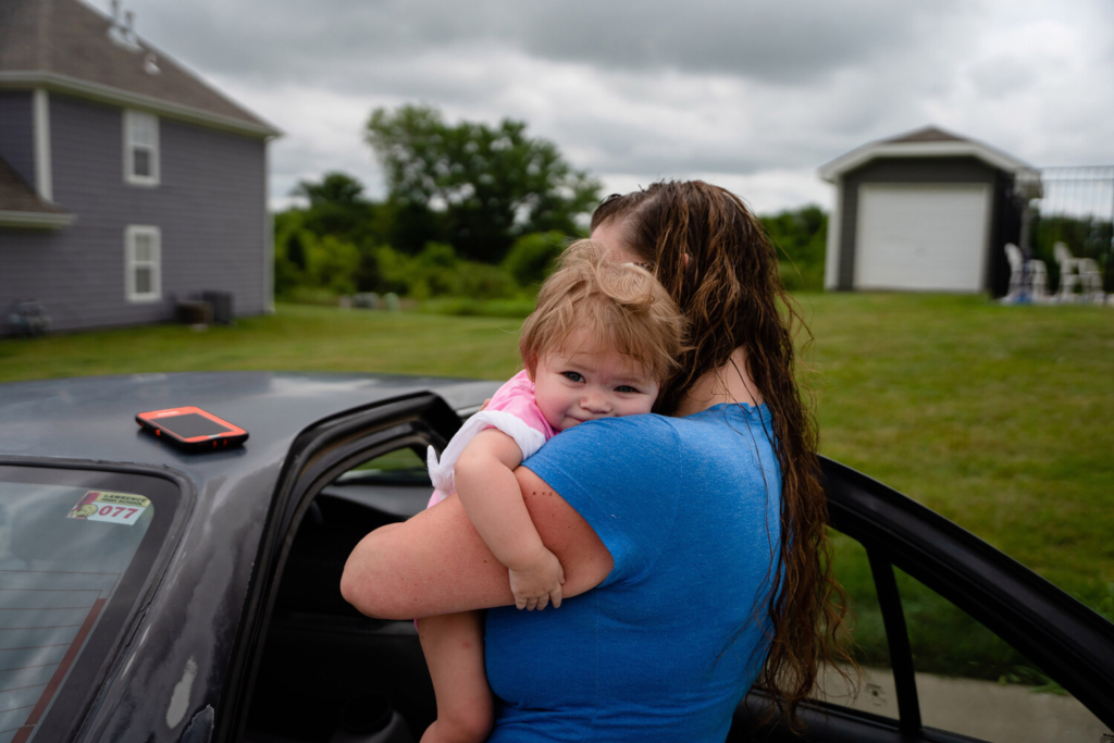 Melissa Markham, a mother of two in Kansas, holds her child, Brooklynn. Markham has lost her home and her job during the coronavirus pandemic, and stringent welfare benefits in the state offer scant relief.