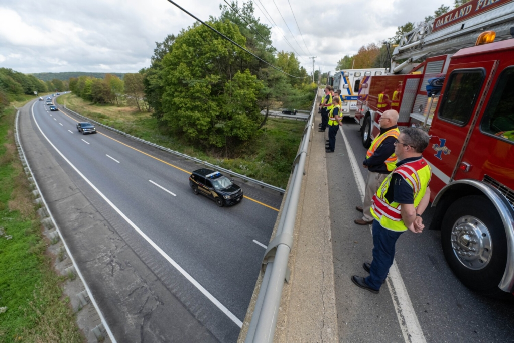 WATERVILLE, MAINE- SEPTEMBER 23, 2021 Shon Dixon, front right, and Tim Beales, back right, both with Delta Ambulance stand above Interstate 95 on Armstrong Road in Waterville on Thursday, Sept. 23, 2021 as a police procession carrying the body of Hancock County Deputy, Luke Gross en route to the State Medical Examiner's office in Augusta. Gross was killed in the early morning hours while responding to a call in Trenton. (Staff Photo by Michael G. Seamans/Staff Photographer)