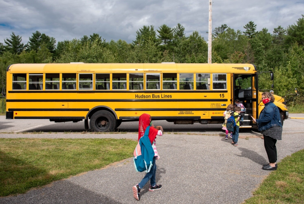 Shawna Haley-Bear, right, helps board the buses on Friday at the McMahon Elementary School in Lewiston. Students are dismissed in groups organized by bus.