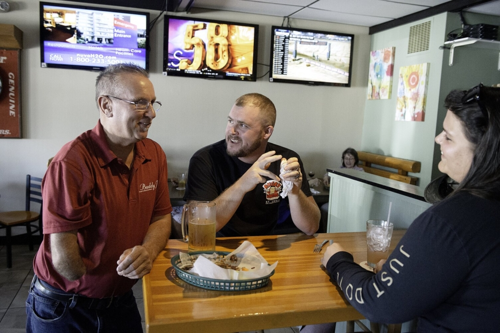 """Buddy Taylor, left, chats with Nathan and Jillian McWilliams on Tuesday at Buddy T's Restaurant and Pub in Lewiston. Taylor's last day at Buddy T's was Tuesday, after owning the business for 16 years. The McWilliamses were married Saturday. """"We are starting our honeymoon here,"""" she said. """"Then heading to New Hampshire."""""""