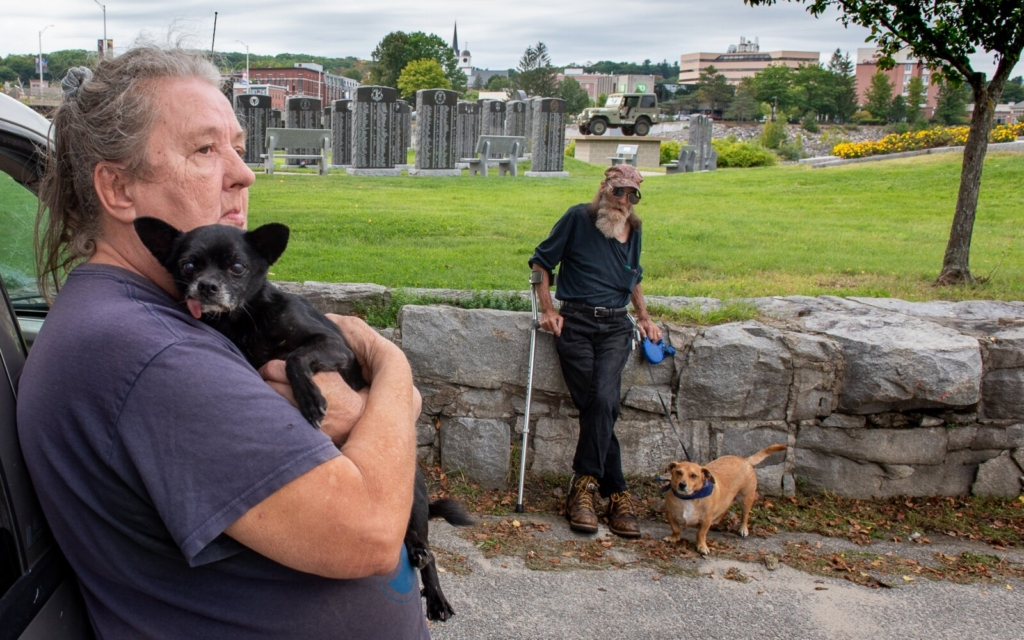 Ann Rivers holds her dog, Gizmo, as she and her husband Paul relax in Veterans Memorial Park in Lewiston Friday afternoon. They have been frustrated trying to find a safe and affordable apartment to live in the twin cities. Their two service dogs, Gizmo and Milky Way, are friendly and well trained but they feel they may be the reason some of the landlords they talked to wouldn't call them back.