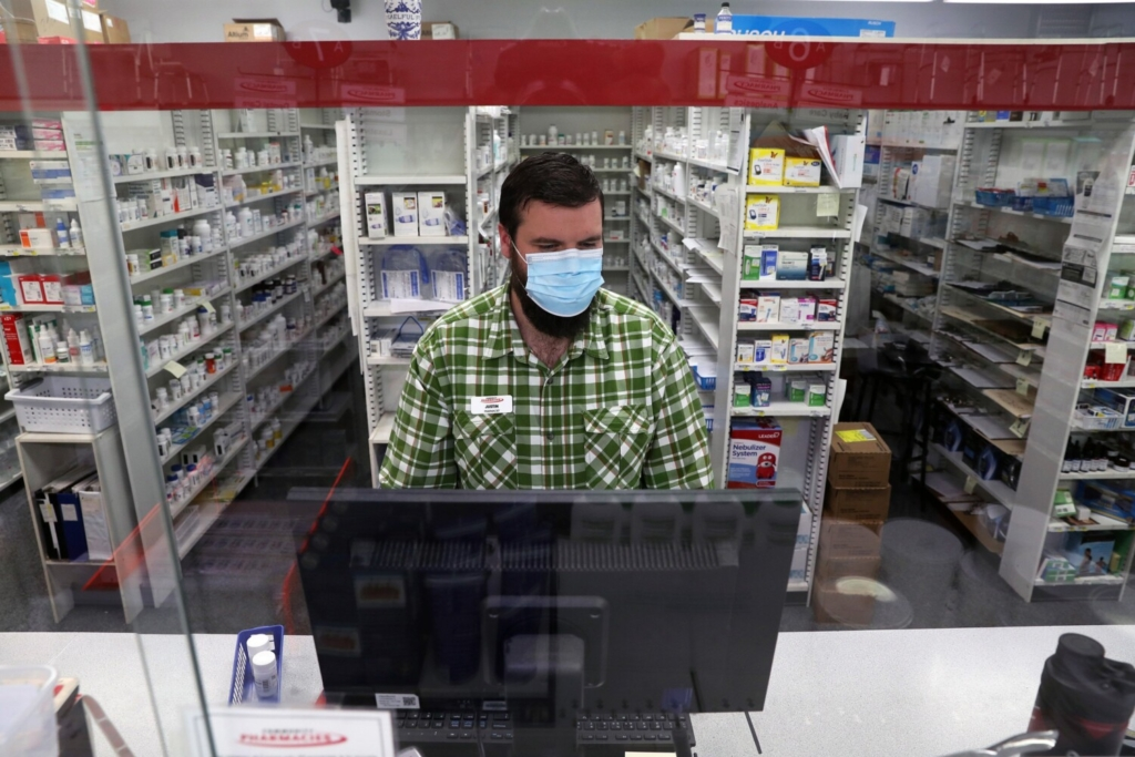 """Justin Richards, a pharmacist at Community Pharmacy of Saco, works behind the counter on Thursday. He said the store receives just 12 packages of Abbott Laboratories' BinaxNOW COVID-19 Ag Card Home Tests per week, and they sell out quickly. """"It's a big bummer because everybody's looking for one,"""" he said."""
