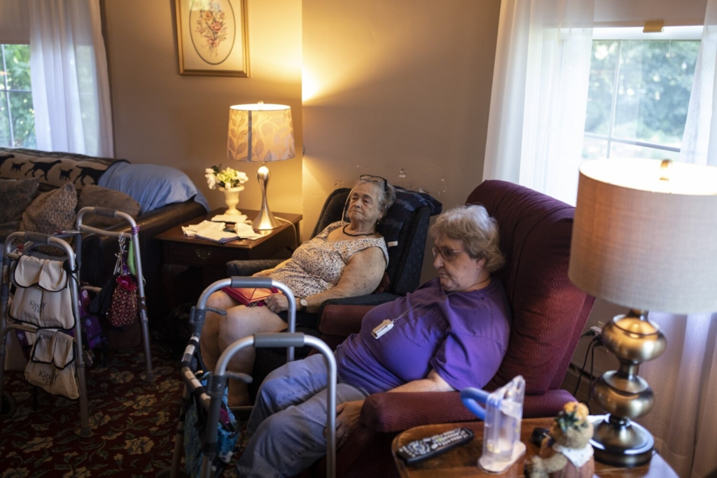 """Darellene Hussey, 82, left, and Velma Newcomb, 77, watch a movie together before lunch Friday at Shaw House Residential Care in Biddeford. The small 20-bed nursing home is closing in the fall for a variety of reasons, but staffing frustrations amid the pandemic were a big factor. Newcomb has lived at the home for about 12 years and Hussey for almost three years. When the home closes, Hussey said she is going to try to get her own place. """"I don't want to move to a big facility,"""" she said. """"I like it here because it is so small."""""""