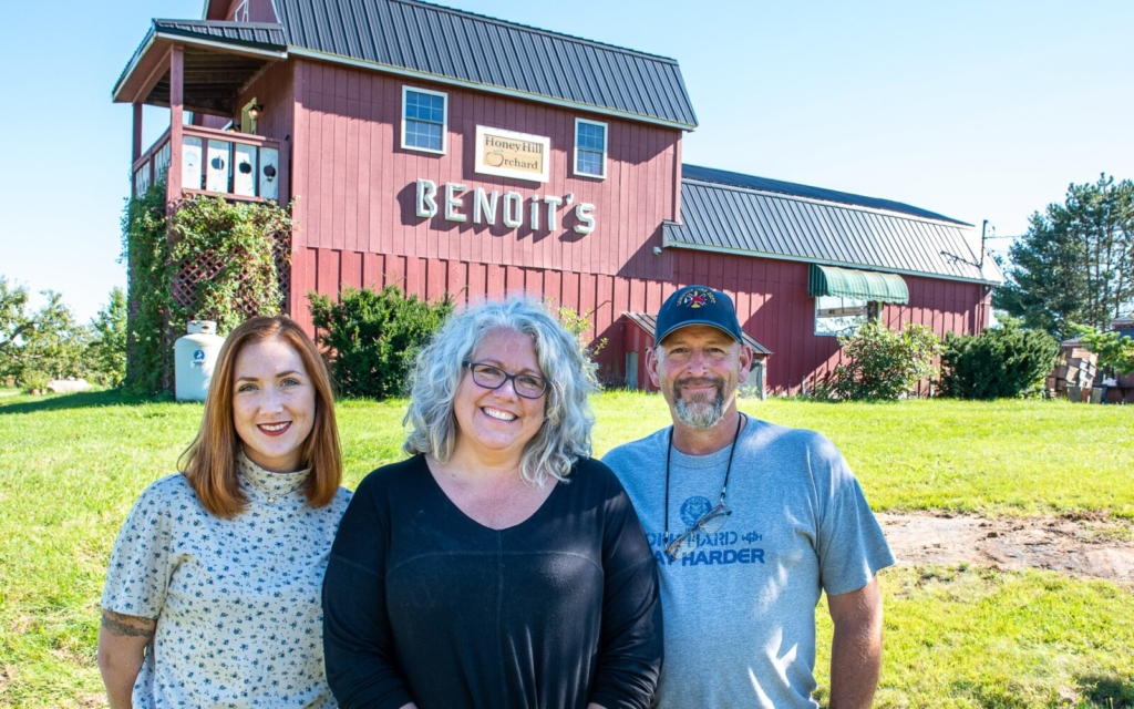 Jennifer Dolloff Barker, middle, husband Jeff Barker, right, and daughter Holly Lavorgna, left, stand Sunday outside the store owned by her son, Sabin Lavorgna, at Honey Hill Orchard on Ferry Road in Lewiston where the former Benoit's Orchard was located.