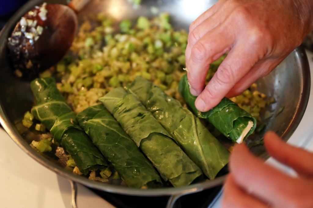 Placing the feta-stuffed rolled collards into the pan to cook.