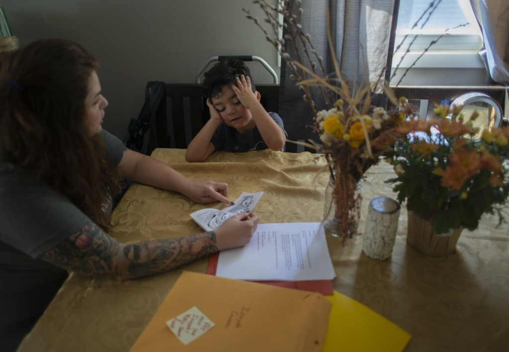 GORHAM, ME - SEPTEMBER 20: Christen Cowper does homework with her son, Izayah, 5, who is in quarantine at home because he was exposed to COVID at school. He has medical conditions that make him more susceptible to severe illness should he catch COVID.. (Photo by Derek Davis/Staff Photographer)