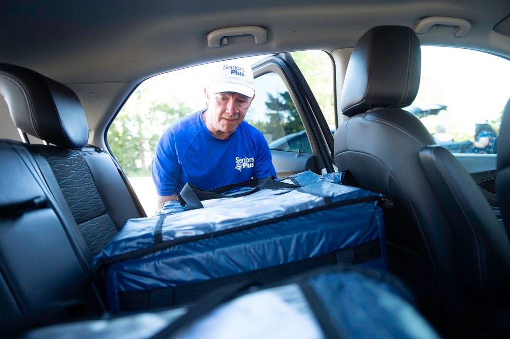 Frank Danforth of Auburn puts meals in the back of his car Tuesday at SeniorsPlus in Lewiston. He volunteers two days a week, making 30 deliveries each Tuesday with the Meals on Wheels program and fewer on Thursdays.