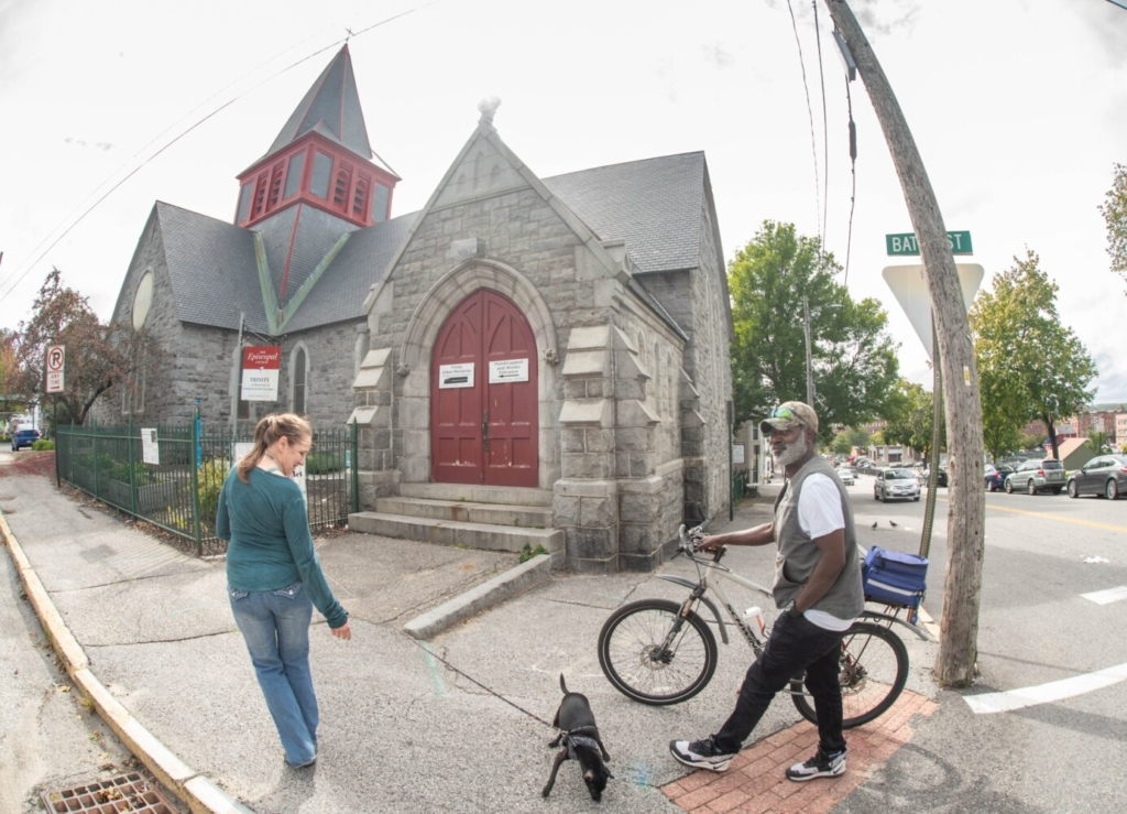 Jeanette Cunningham walks with her friend Lee Heath on Wednesday along the sidewalk in front of the Trinity Jubilee Church in Lewiston. Plans are in the works to turn Trinity Church into a community center, expanding Trinity Jubilee in the basement and adding new elements upstairs.