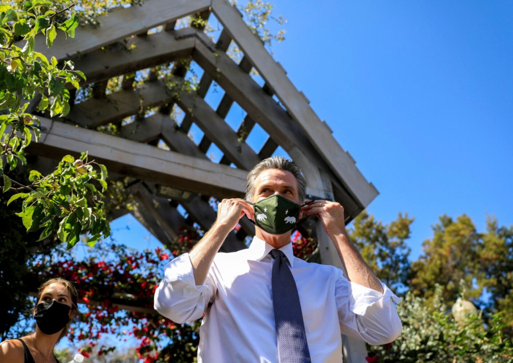 """California Gov. Gavin Newsom adjusts his face mask during a rally at St. Mary's Center in Oakland, Calif., Saturday, Sept. 11, 2021. The last day to vote in the recall election is Tuesday, Sept. 14. A majority of voters must mark """"no"""" on the recall to keep Newsom in office. (Shae Hammond/Bay Area News Group via AP)"""