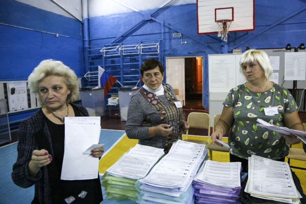 Members of an election commission prepares to count ballots after voting at a polling station after the Parliamentary elections in Nikolayevka village outside Omsk, Russia, Sunday, Sept. 19, 2021. From the Baltic Sea to the Pacific Ocean, Russians across eleven time zones voted Sunday on the third and final day of a national election for a new parliament, a ballot in which the pro-Kremlin ruling party is largely expected to retain its majority after months of relentless crackdown on the opposition. (AP Photo/Evgeniy Sofiychuk)