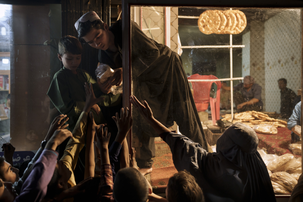 Afghan children and women gather outside a bakery Friday to get free bread in Kabul, Afghanistan.