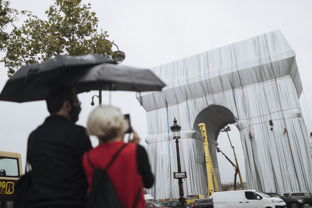 """Workers wrap the Arc de Triomphe monument on Wednesday """"L'Arc de Triomphe, Wrapped"""" project by late artist Christo and Jeanne-Claude will be on view from, Sept. 18 to Oct. 3."""