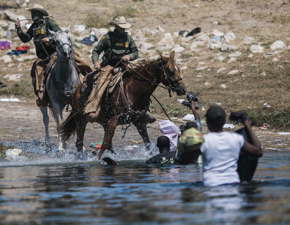 U.S. Customs and Border Protection mounted officers attempt to contain migrants as they cross the Rio Grande from Ciudad Acuña, Mexico, into Del Rio, Texas, Sunday, Sept. 19.
