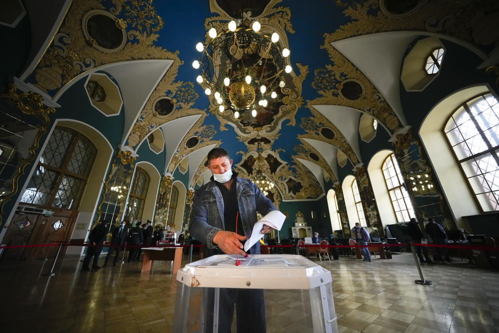 A man casts his ballot at a polling station at the Kazansky railway station during the Parliamentary elections in Moscow, Russia, Saturday, Sept. 18.