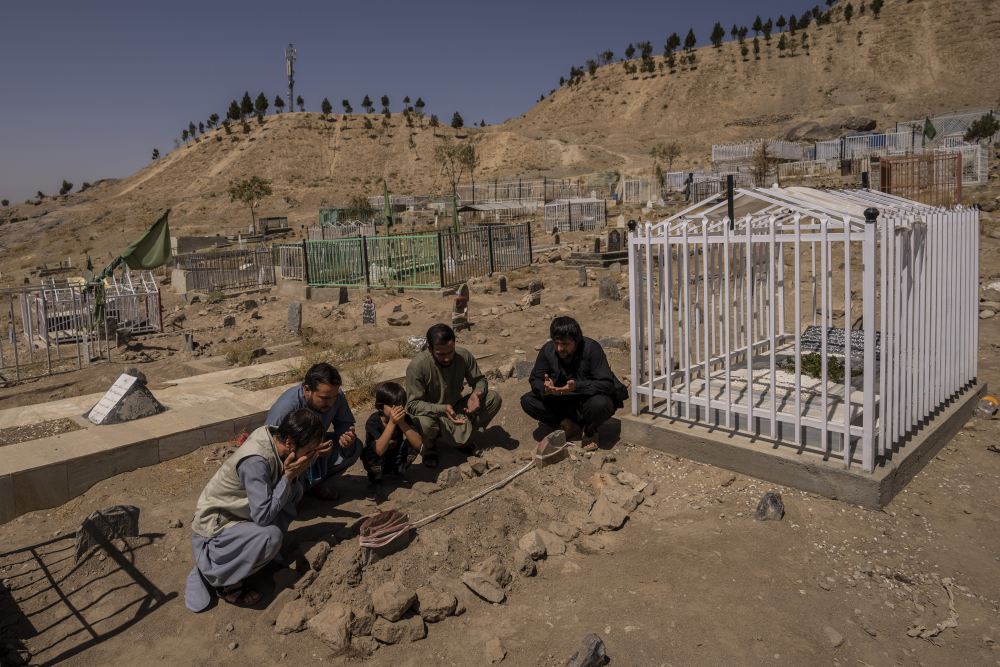 The Ahmadi family prays last week next to graves of family members killed by a U.S. drone strike, in Kabul, Afghanistan.   Sorry is not enough for the Afghan survivors of an errant U.S. drone strike that killed 10 members of their family, including seven children. (AP Photo/Bernat Armangue, File)