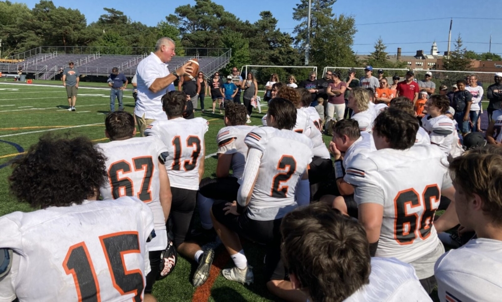 Biddeford Coach Steve Allosso gets emotional as he talks to his team Saturday after they awarded him the game ball following a 36-14 win at Deering. It was Allosso's first game as the Tigers' head coach.