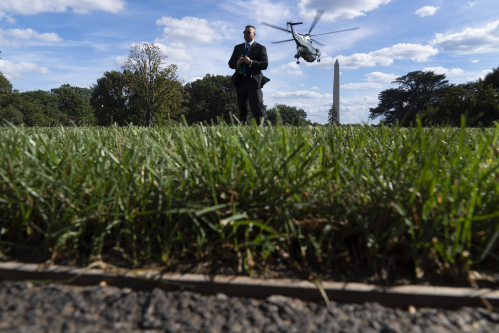 A Secret Service agent stands guard as Marine One with President Biden abroad lifts off from the South Lawn of the White House in Washington on Monday.