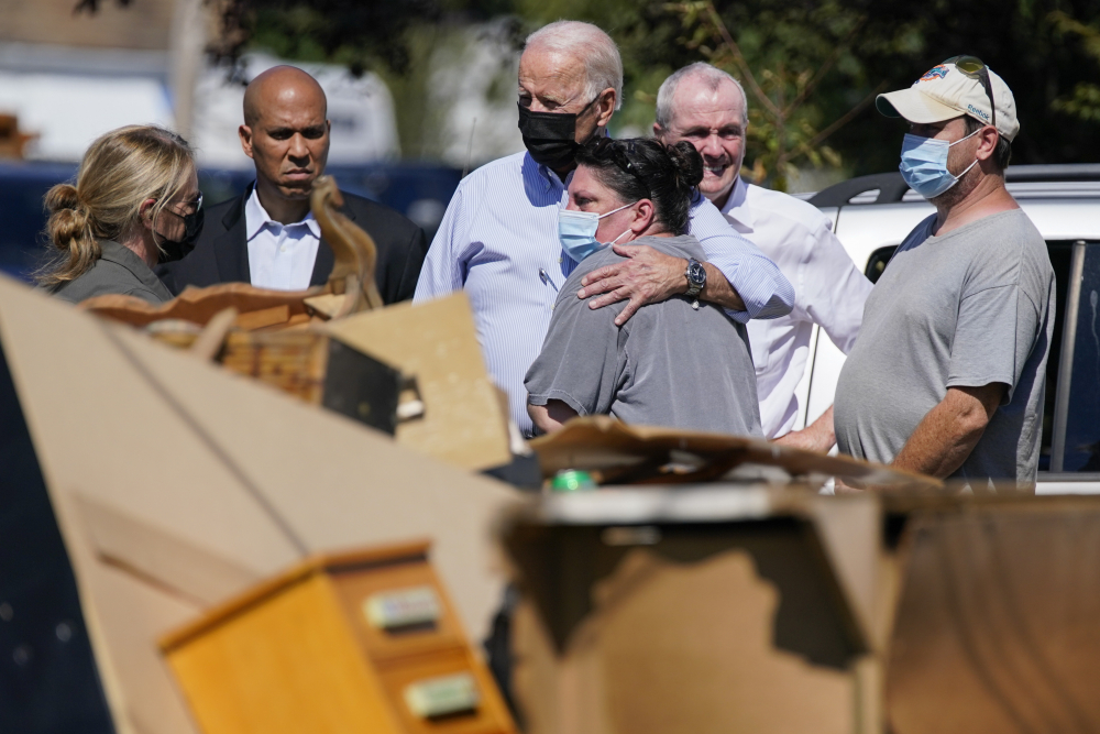 President Joe Biden hugs a person as he tours a neighborhood impacted by Hurricane Ida, Tuesday, Sept. 7, 2021, in Manville, N.J. Sen. Cory Booker, D-N.J., second from left, and New Jersey Gov. Phil Murphy, second from right, look on.