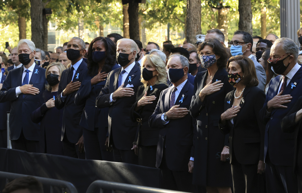 From left, former President Bill Clinton, former First Lady Hillary Clinton, former President Barack Obama, Michelle Obama, President Biden, first lady Jill Biden, former New York City Mayor Michael Bloomberg, Bloomberg's partner Diana Taylor, Speaker of the House Nancy Pelosi, D-Calif., and Senate Majority Leader Charles Schumer, D-N.Y., stand for the national anthem during the annual 9/11 Commemoration Ceremony at the National 9/11 Memorial and Museum on Saturday in New York.