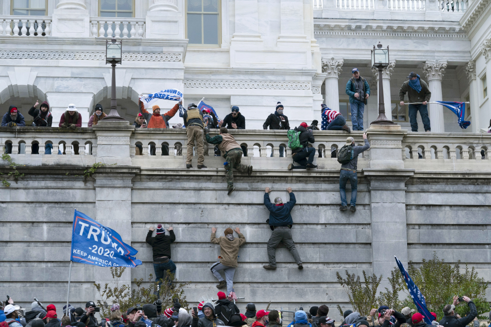 Violent insurrectionists loyal to President Donald Trump scale the west wall of the the U.S. Capitol in Washington on Jan. 6.