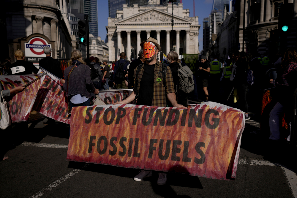 An Extinction Rebellion climate change activist holds a banner backdropped by the Bank of England, at left, and the Royal Exchange, center, in the City of London financial district in London on Sept. 2, 2021.