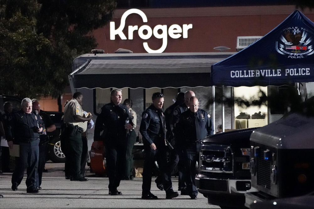 Law enforcement personnel work in front of a Kroger grocery store as an investigation goes into the night following a shooting earlier in the day on Thursday in Collierville, Tenn. Police say a gunman attacked people in the store and killed at least one person and wounded 12 others before the suspect was found dead.
