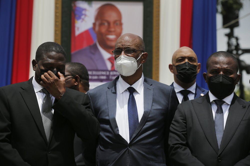 Haiti's designated Prime Minister Ariel Henry, center, and interim Prime Minister Claude Joseph, right, pose for a group photo with other authorities in front of a portrait of slain Haitian President Jovenel Moise at the National Pantheon Museum during a memorial service for Moise in Port-au-Prince, Haiti, in July. Haiti's chief prosecutor has asked a judge to charge Henry in the slaying of Moise and barred him from leaving the country.