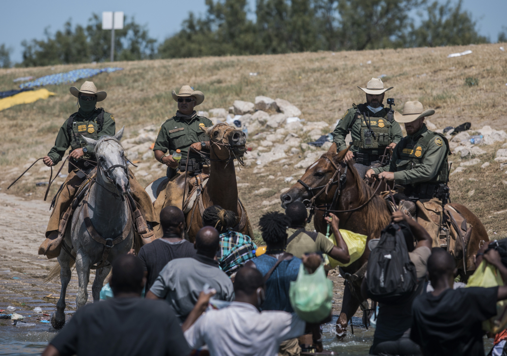 U.S. Customs and Border Protection mounted officers attempt to contain migrants as they cross the Rio Grande from Ciudad Acuña, Mexico, into Del Rio, Texas, on Sunday. Thousands of Haitian migrants have been arriving in Del Rio as authorities attempt to close the border to stop the flow of migrants.
