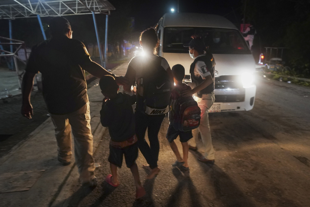 Mexican immigration agents detain a Central American migrant who is part of a caravan heading north in Huixtla, Chiapas state, on Sunday