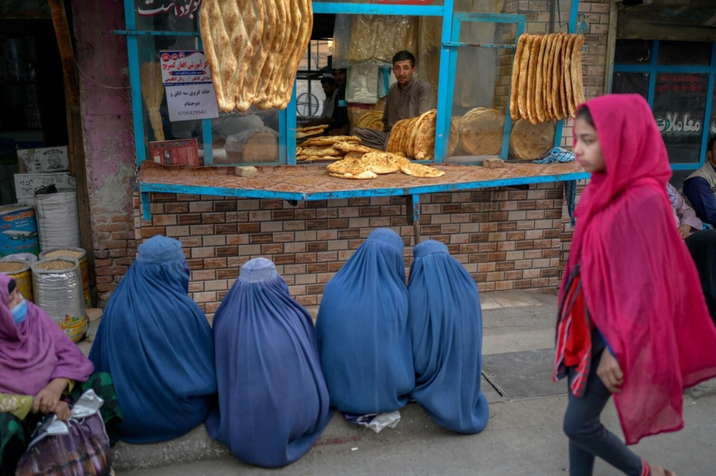 Burqa-clad women wait for free bread in front of a bakery in Kabul, Afghanistan, on September 16, 2021. (Bulent Kilic/AFP/Getty Images/TNS)