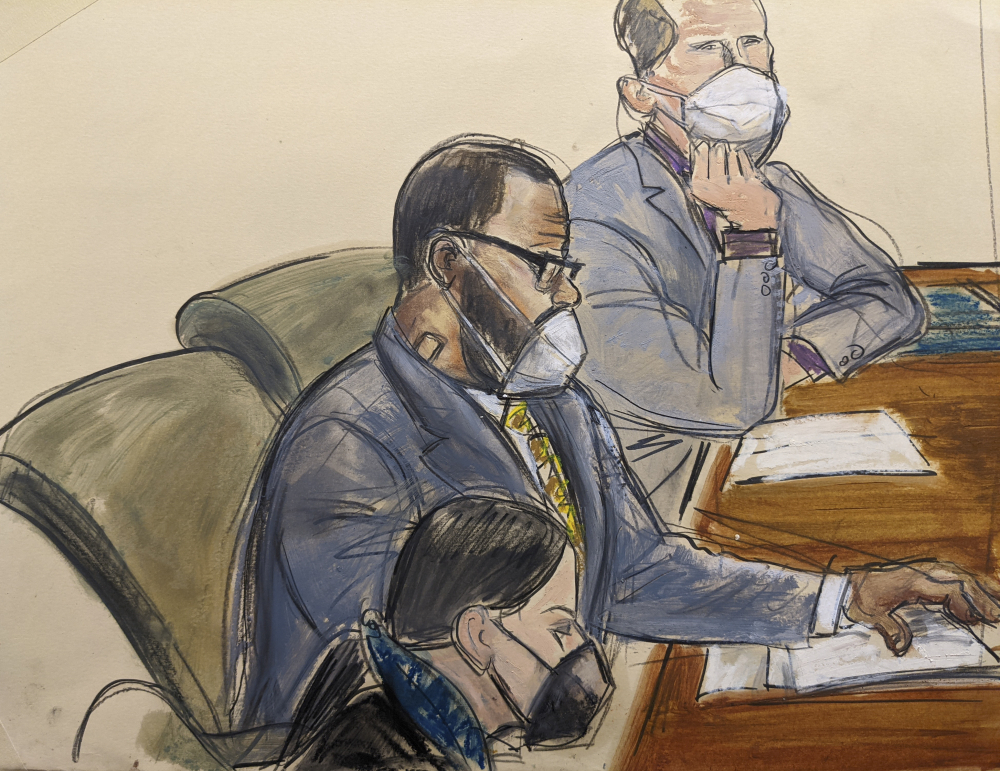 In this courtroom sketch, R. Kelly, center, sits with his defense attorneys Thomas Farinella, top, and Nicole Blank Becker during the first day of his defense in his sex trafficking case, Monday in New York.
