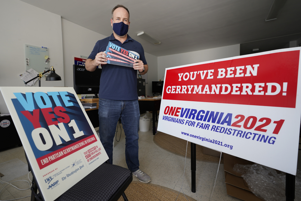 Redistricting reform advocate Brian Cannon poses with some of his yard signs and bumper stickers in his office in Richmond, Va., in 2020. A new voter-approved commission in Ohio that was supposed to reduce partisanship in the once-a-decade process of political map-drawing has already become a flop.