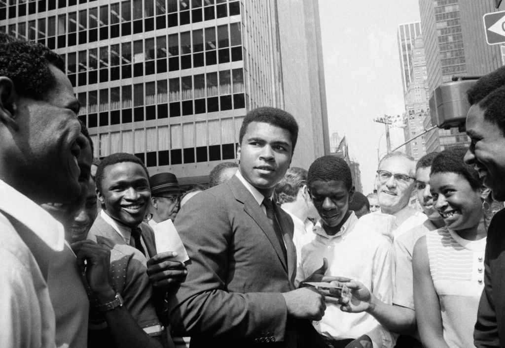 Muhammad Ali, former world heavyweight boxing champion, is surrounded by autograph seekers at 51st Street and Sixth Avenue in Manhattan borough of New York, Aug. 23, 1968. He was en route to a television studio when pedestrians mobbed him. The former champ says he may fight Joe Frazier on an Indian reservation, which he claims would not place such a bout under government control. (AP Photo/Anthony Camerano)