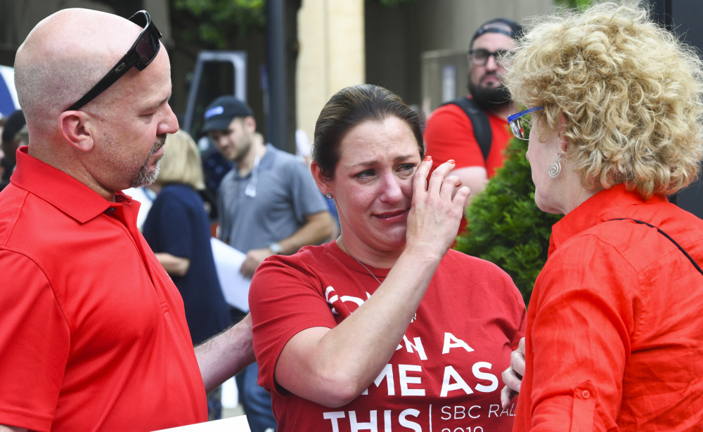 Jules Woodson, center, of Colorado Springs, Colo., is comforted by her boyfriend Ben Smith, left, and Christa Brown while demonstrating outside the Southern Baptist Convention's annual meeting in Birmingham, Ala. on June 11, 2019. First-time attendee Woodson spoke through tears as she described being abused sexually by a Southern Baptist minister.