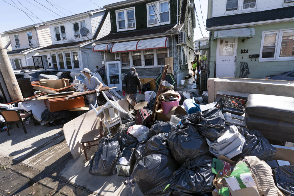 People clear debris and damaged belongings from their homes in the Queens borough of New York on Sept. 3.
