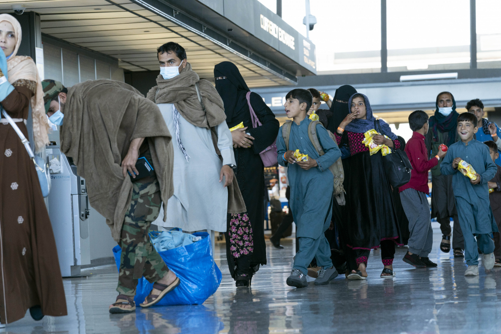 People evacuated from Kabul, Afghanistan, walk through the terminal before boarding a bus after they arrived at Washington Dulles International Airport, in Chantilly, Va., on Thursday, Sept. 2.
