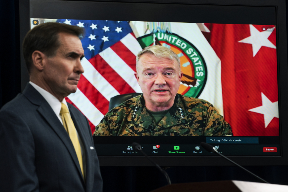 Gen. Frank McKenzie, commander of U.S. Central Command, appears on screen as he speaks from MacDill Air Force Base in Tampa, Fla., in August. At left is Pentagon spokesman John Kirby.