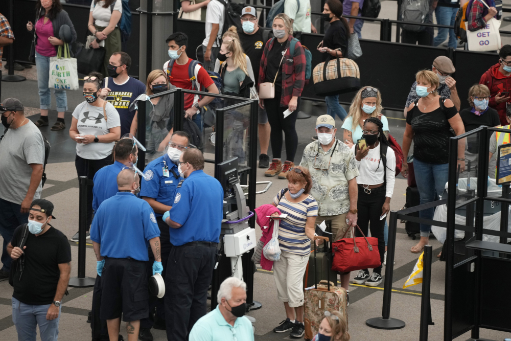 Travelers wear face coverings while waiting in line for a security checkpoint in the main terminal of Denver International Airport in August in Denver.