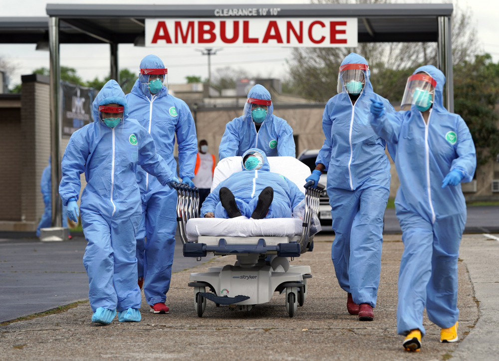 A patient is taken on a stretcher into the United Memorial Medical Center  after going through testing for COVID-19 in Houston in March 2020, as the coronavirus pandemic began tightening its grip on the U.S. People were lined up in their cars in a line that stretched over two miles to be tested in the drive-thru testing for coronavirus.