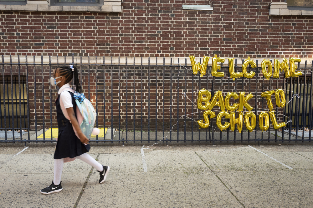 """A girl passes a """"Welcome Back to School"""" sign on Sept. 13 as she arrives for the first day of class at Brooklyn's PS 245 elementary school in New York."""