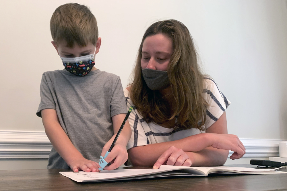 Emily Goss goes over schoolwork at the kitchen table with her 5-year-old son at their Monroe, N.C., home on Monday. The Gosses have decided to home-school Berkeley after the Union County school district chose not to implement a mask mandate for children.