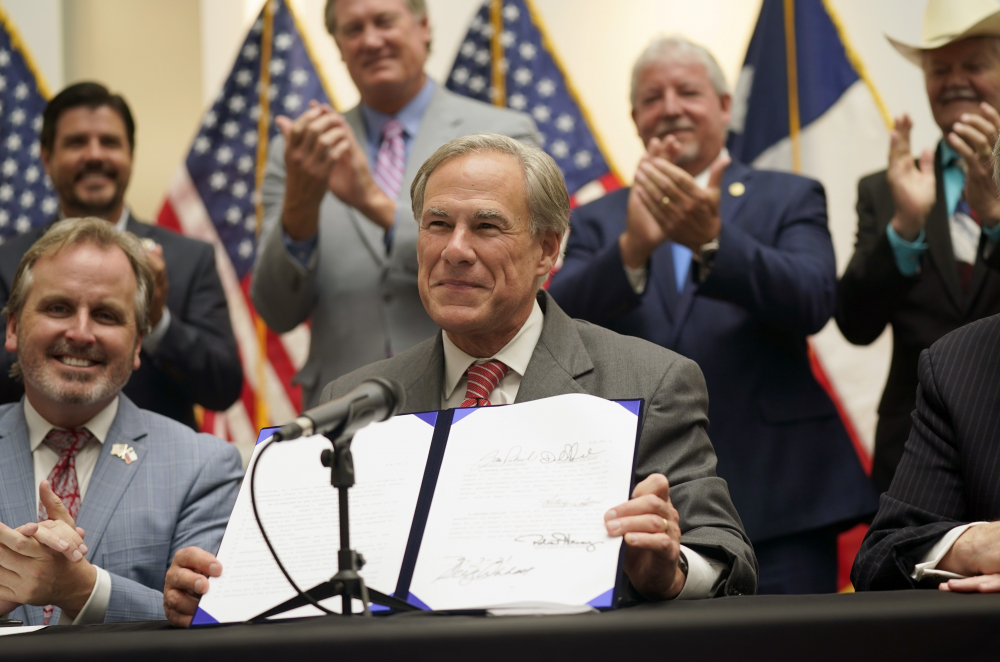 Texas Gov Greg Abbott shows off Senate Bill 1 after he signed it into law in Tyler, Texas, Tuesday, Sept. 7, 2021. The sweeping bill signed Tuesday by the two-term Republican governor further tightens Texas' strict voting laws.