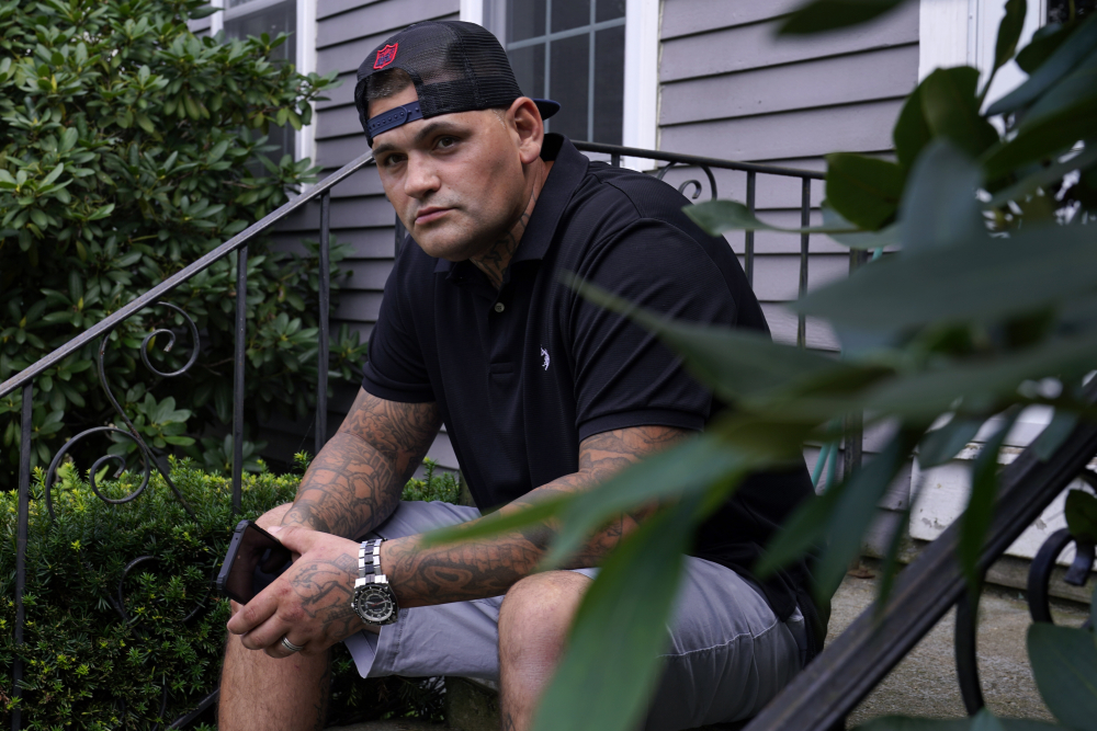 Mike Gilpatrick, who as a teenager was incarcerated at the Youth Development Center, poses on the front steps of his home, Wednesday, Sept. 8, 2021, in Nashua, N.H.