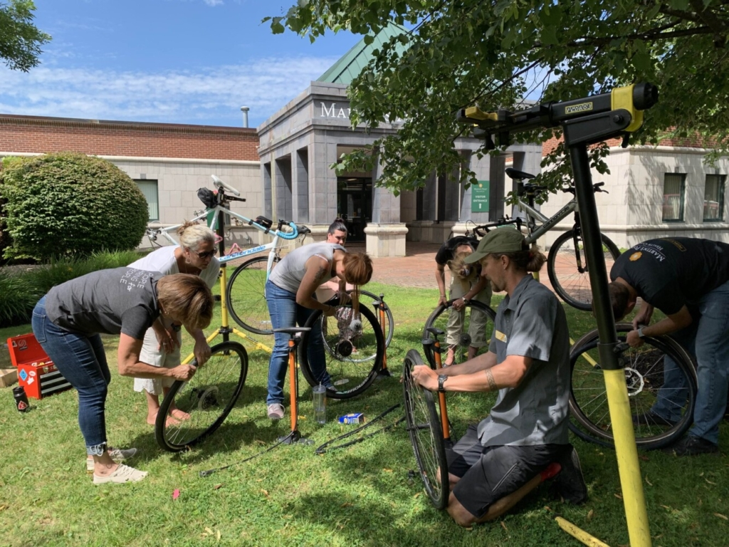 """Shannon Bell of the Bicycle Coalition of Maine, center foreground, leads one of the organization's """"Fix-A-Bike"""" workshops in 2019 outside of Martin's Point Health Care in Portland. The pictured workshop was prior to the COVID-19 pandemic."""
