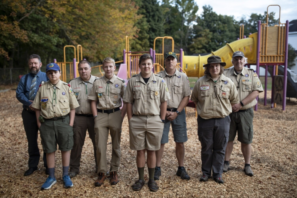 BUXTON, ME - SEPTEMBER 30: From left, Chad Poitras, Mathieu Poitras, 12, Danny Rose, Sawyer Rose, 13, Luke Plummer, 16, Garrett Plumner, Nicholas Hobson, 16, and Eric Hobson pose for a portrait in front of the the Eliza Libby School playground on Thursday, September 30, 2021. The school closed about a decade ago the playground was completely overgrown. Plummer, a junior at Bonny Eagle, took on overseeing the playground's restoration - his community project to become an Eagle Scout and he did the work alongside members from his Boy Scout Troop 349 and many of their family members. (Staff photo by Brianna Soukup/Staff Photographer)