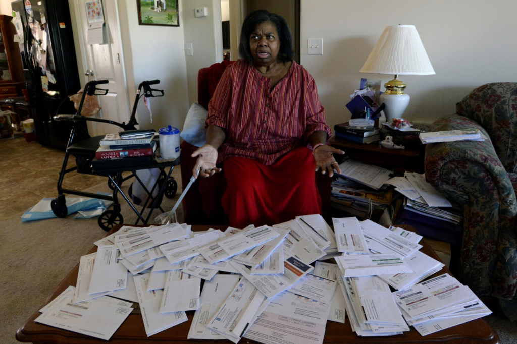 Debra Smith, 57, talks about her medical bills in her living room on Thursday, Oct. 7, 2021, in Spring Hill, Tenn. Smith has around $10,000 in unpaid medical bills from a string of hospital stays over the past year, even though she has coverage through Medicare. She hasn't been able to make much progress paying them off. (AP Photo/Mark Zaleski)