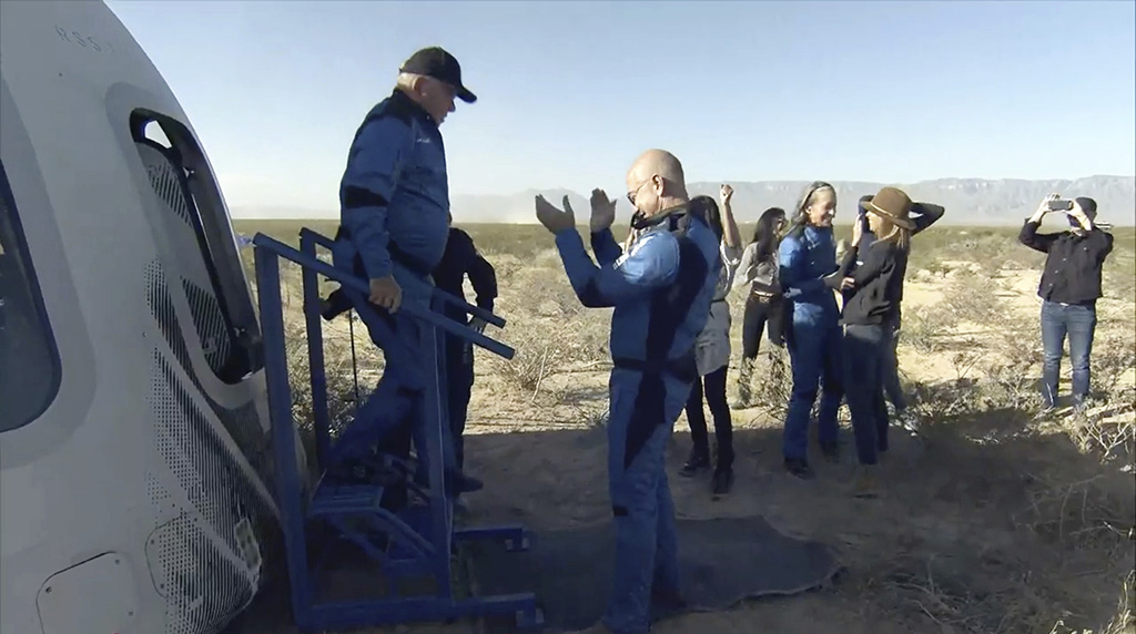 """In this image provided by Blue Origin, William Shatner exits the Blue Origin capsule as he is greeted by Jeff Bezos near Van Horn, Texas, Wednesday, Oct. 13, 2021.  The """"Star Trek"""" actor and three fellow passengers hurtled to an altitude of 66.5 miles (107 kilometers) over the West Texas desert in the fully automated capsule, then safely parachuted back to Earth in a flight that lasted just over 10 minutes.  (Blue Origin via AP)"""