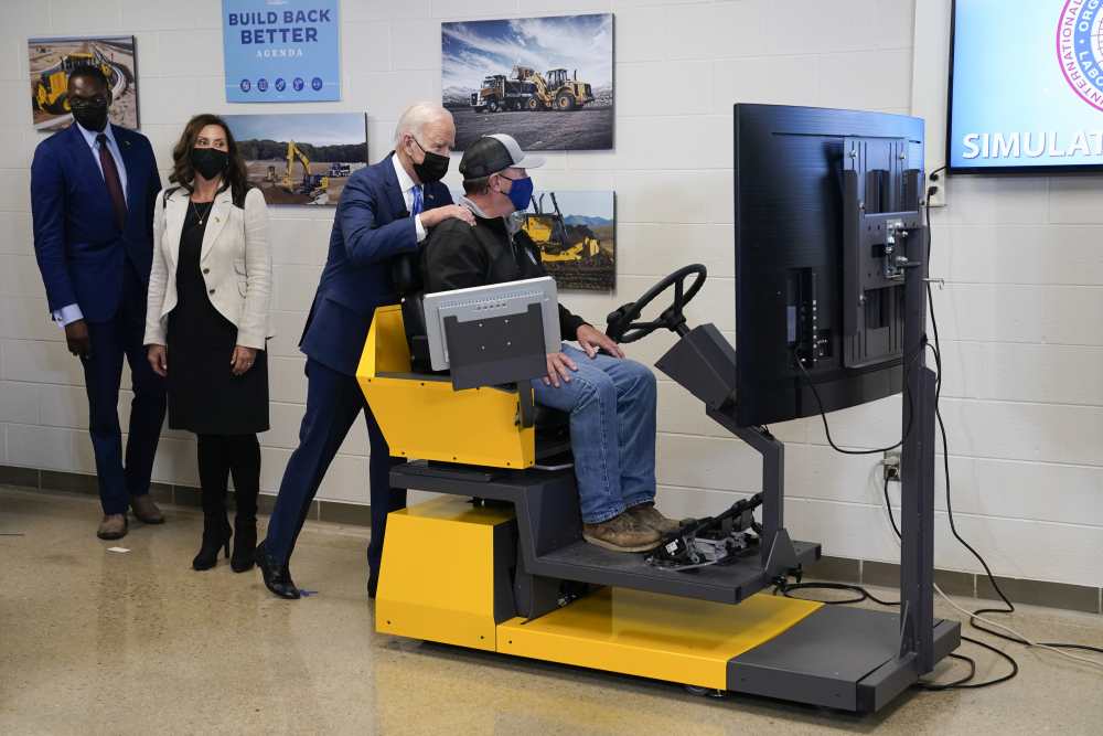 President Biden tours the International Union Of Operating Engineers Local 324 training facility on Tuesday in Howell, Mich. Michigan Lt. Gov. Garlin Gilchrist, left, and Michigan Gov. Gretchen Whitmer, second from left, accompany him.
