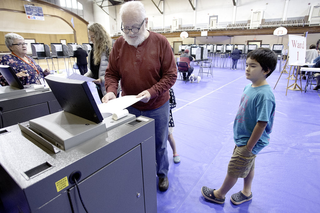 Jon Pitman casts his ballot at the Lewiston Memorial Armory. The merger vote was on the ballot. (Sun Journal file photo)