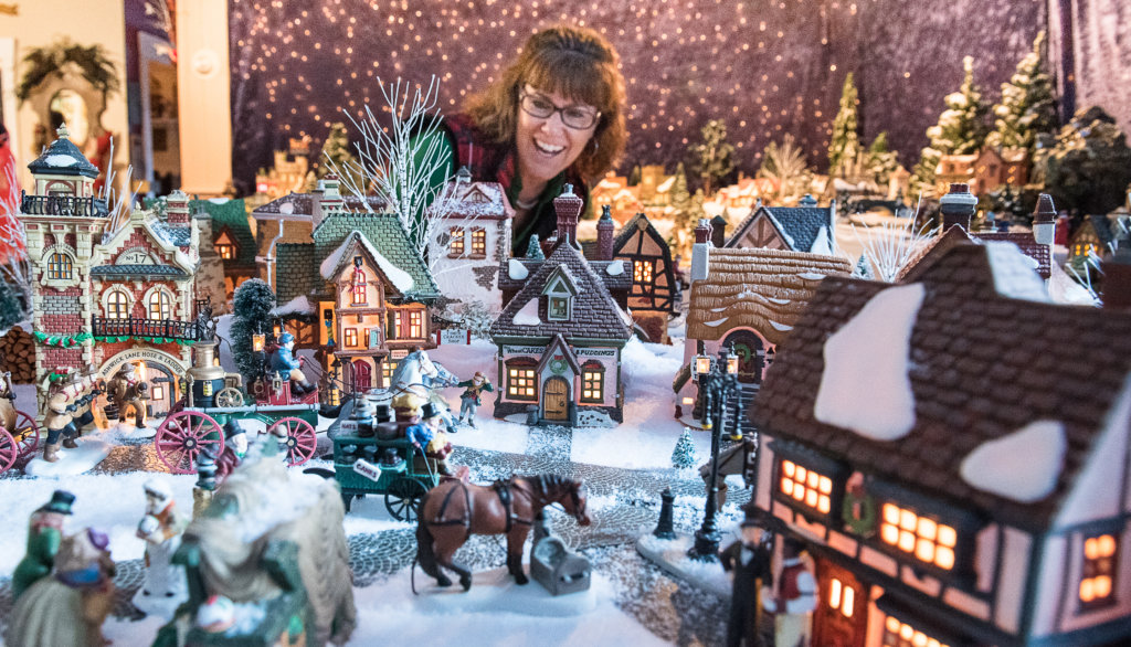 "Patti Gagne of Lewiston admires the ""Dickens Village"" display at the home of her friends Richard and Mary LaFontaine during Monday's open house in Auburn."